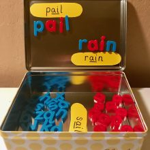 Phonics metal box and magnetic letters to create phonogram 'ai' words